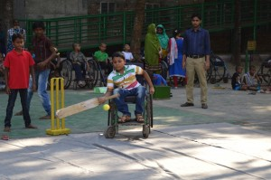 A young boy in a wheelchair is hitting a ball with a bat.